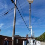 TALL ORDER: The Partnership for Rhode Island Streetlight Management, founded and led by Jeffrey A. Broadhead, left, is helping cities and towns find significant savings by converting streetlights to light-emitting diodes. Installing a new light in Providence is electrician Jim Mitchell.
