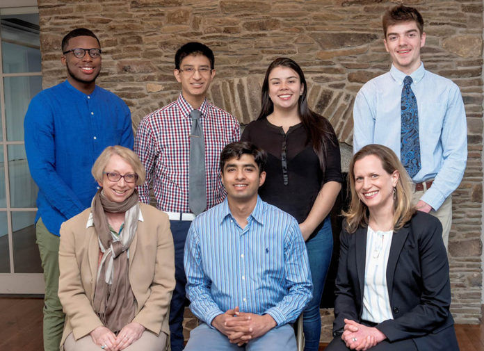 """UNIVERSITY OF Rhode Island engineering students, back row, from left, Corvah Akoiwala, Cristian Witcher, Laura Parra and James Gannon, will travel to Colombia this summer with prosthetic arms and hands they have made for amputees. The project is funded by a federal grant from the """"100,000 Strong in the Americas"""" program. In the front row are, from left, Sigrid Berka, director of the International Engineering Program at URI; Kunal Mankodiya, assistant professor of biomedical engineering at URI; and Silke Scholz, director of the Spanish International Engineering Program at URI. / COURTESY UNIVERSITY OF RHODE ISLAND/MICHAEL SALERNO"""