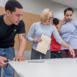 TEACHABLE MOMENTS: Brickle Group employees Roddy Rodriguez, left, and Belanie Medina, right, take part in a Manufacturing Center of Excellence class being taught at the New England Institute of Technology by mechanical-engineering instructor Annie Unger. / PBN PHOTO/MICHAEL SALERNO