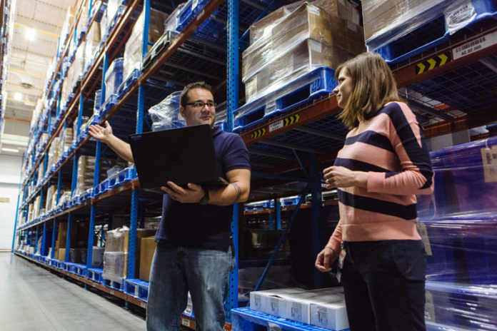 MEETING TIME-CRITICAL NEEDS: Joe Aguiar, left, senior associate, supply chain, and Kacey Fetcho, senior manager, supply chain, inspect inventory at Amgen Rhode Island's West Greenwich manufacturing facility. / PBN PHOTO/RUPERT WHITELEY