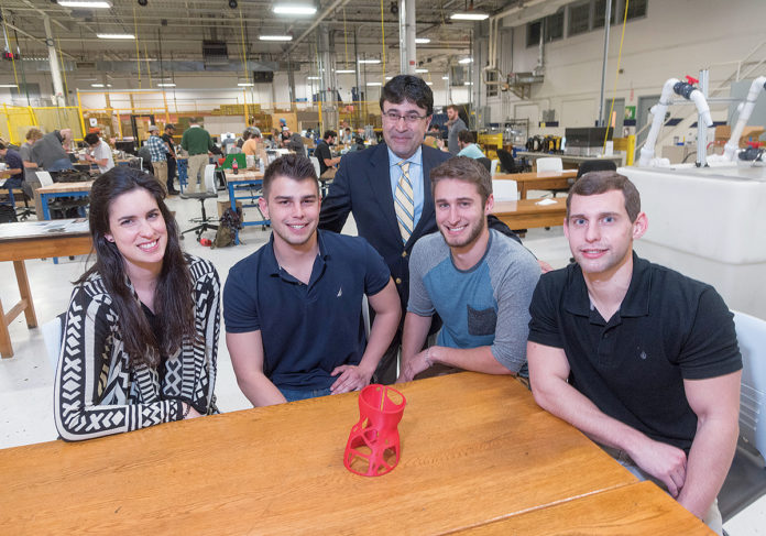 INNOVATIVE DESIGN: University of Rhode Island engineering students designed a new scoliosis brace and printed a 1/25-scale model prototype on a 3-D printer. From left, Gabriella Divine, a fifth-year mechanical-engineering and Spanish major from East Greenwich; Chris Viveiros, a mechanical-engineering senior from Attleboro; URI professor Bahram Nassersharif; Dan Cross, a mechanical-engineering senior from Northborough, Mass.; and Thomas Brey, a mechanical-engineering senior from Manville, N.Y. / PBN PHOTO/MICHAEL SALERNO