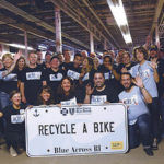 A PASSION FOR CARING: Blue Cross & Blue Shield of Rhode Island employees are given eight hours of paid time per year to volunteer. Here, they volunteer at Recycle-A-Bike in Cranston. / COURTESY BLUE CROSS & BLUE SHIELD OF RHODE ISLAND