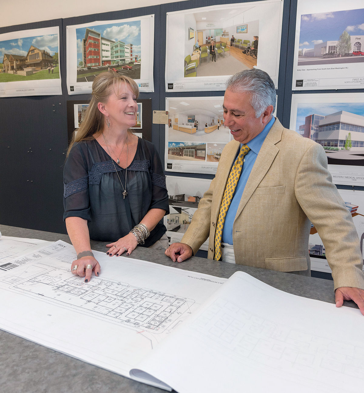 SEEKING WORK PRODUCT RESPECT: Jennifer Space, an associate at n e m d architects inc., and president of the Rhode Island branch of the American Institute of Architects, looks over some plans with n e m d architects President Mehdi Khosrovani. Space believes local firms are bypassed too often for high-profile work. / PBN PHOTO/MICHAEL SALERNO