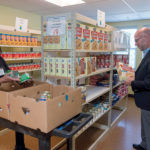 INCREASED RELIANCE: Rhode Island Community Food Bank CEO Andrew Schiff helps volunteer Yve Capella stock the shelves at The Olneyville Food Center at 261 Manton Ave., in Providence. Schiff says there is an increased reliance on emergency food pantries fed by the food bank in the summer months when free and reduced-priced school-meal services are paused, putting greater strain on low-income families to afford food. / PBN PHOTO/MICHAEL SALERNO