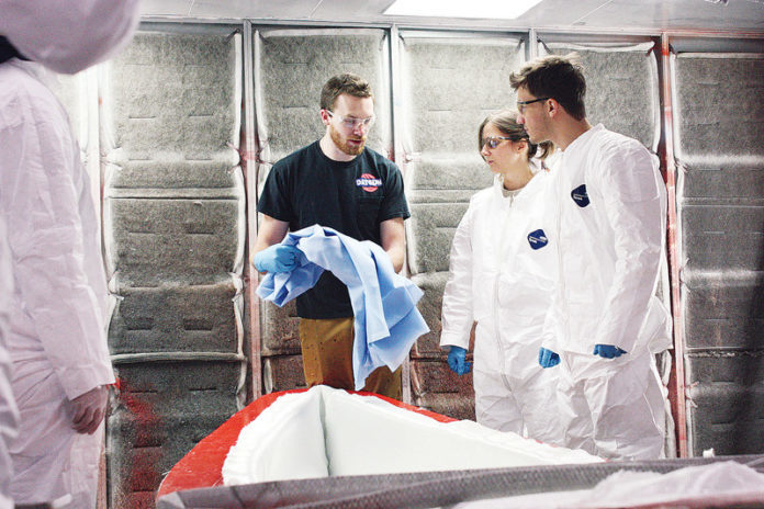 IYRS SCHOOL OF Technology and Trades student Andrew Leonard, black T-shirt, shows Massachusetts Institute of Technology students Carrie McKnelly and Tyler Crain how to prepare a mold for a lightweight canoe. The IYRS campus in Bristol is one example of the East Bay's concentration of composites expertise, which a new $125,000 federal grant from the U.S. Economic Development Administration aims to tap into. /COURTESY MICHAEL CAMERON