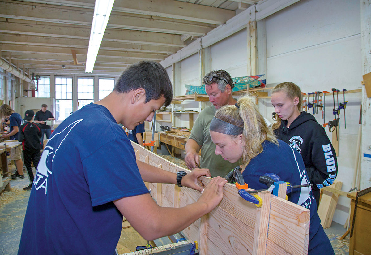 SKIFF WORK: Kirk Cusic, green shirt, executive director of the Herreshoff Marine Museum in Bristol, works with students on a traditional Westport skiff, as part of the Rhode Island Marine Trades Association's Youth Summer Boatbuilding Program.  / COURTESY RIMTA/BILLY BLACK