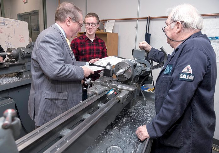 IN THE CLASSROOM: Steven H. Kitchin, left, New England Institute of Technology vice president for corporate education and training, speaks with Kaleb Buffum, a student in the Shipbuilding Advanced Manufacturing Institute program, while instructor Wayne Farmer looks on at the facility on Post Road in Warwick. / PBN PHOTO/MICHAEL SALERNO