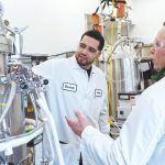SAFETY BRIEFING: Devon Zayas, left, and Scott Lyons, senior associates in the process-development division at Amgen's laboratory in West Greenwich, conduct a pre-job safety briefing for hand-valve manipulations on the 100-liter stainless-steel bioreactor. / PBN PHOTO/RUPERT WHITELEY