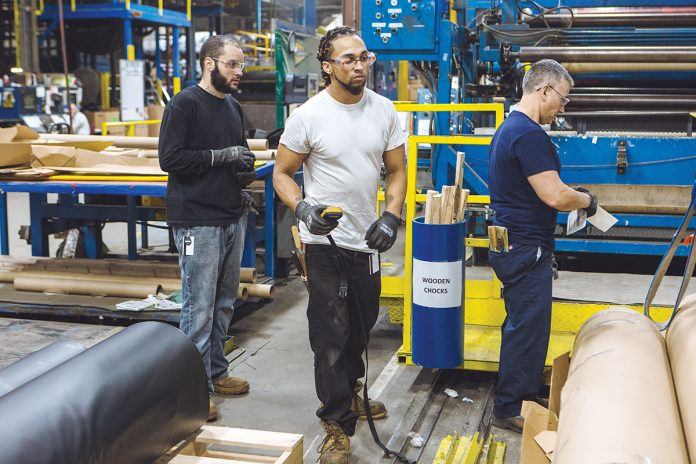 ON A ROLL: From left, Cooley Group employees Bo LeBlue, Cas Pereira and Joe Mello convert a finished goods roll of CoolGuard liner material, often used to line reservoirs, to the proper size.   / PBN PHOTO/RUPERT WHITELEY