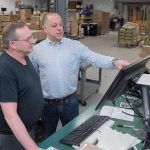 BOARDS REVIEWED: From left, Randy Broyles, shipper, and CEO Edward McMahon look at the orders going out at Epec Engineered Technologies. / PBN PHOTO/MICHAEL SALERNO