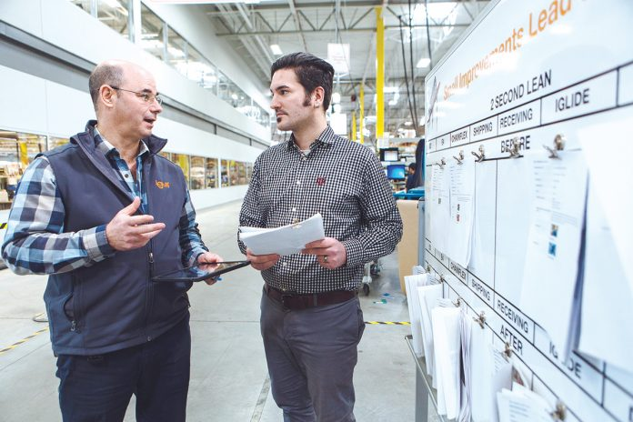 SAFETY THIRST: From left, Gerry Fournier, operations manager, and Mathiew Medeiros, digital marketing specialist, discuss safety tips submitted via the igus iPad safety app. / PBN PHOTO/RUPERT WHITELEY