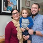 MAKING MEMORIES: Ivette Luna, lead consumer-engagement specialist at Blue Cross & Blue Shield of Rhode Island, with her 2-year-old son Daniel and husband, Jose. The family portrait on the wall was taken during a trip to the Dominican Republic. / PBN PHOTO/MICHAEL SALERNO