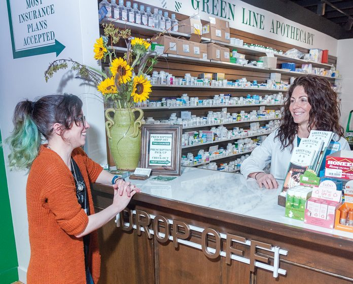 MODERN CLASSIC: Pharmacist Christina Procaccianti, right, operates a modern version of a classic American drugstore. Green Line Apothecary is on Main Street in South Kingstown. Above, she talks with Laura Taylor of Exeter at the drop-off counter. / PBN FILE PHOTO/MICHAEL SALERNO