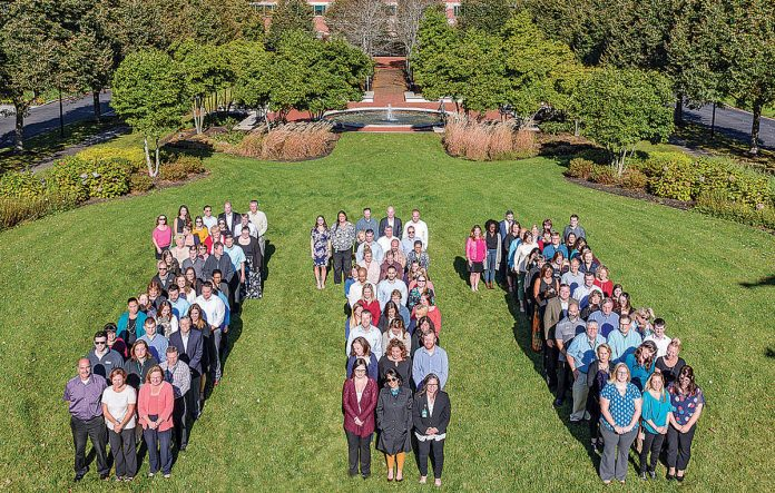 CELEBRATION OF THE CENTURY: Amica employees celebrate the company's 111th anniversary in Amica's Lincoln campus courtyard. / COURTESY AMICA