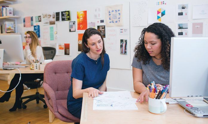 DESIGN TEAM: Sarah Rainwater, center, founder, president and creative director of Studio Rainwater, talks with designer Danikqwa Rambert, right, at the firm's office in East Providence. Art Director Sarah Verity works in the background. / COURTESY STUDIO RAINWATER