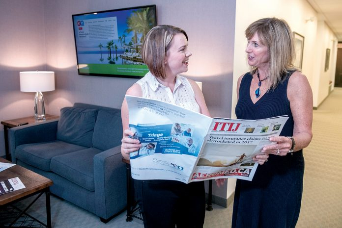 CUSTOMER FOCUS: Ronni Kenoian, left, marketing manager for InsureMyTrip.com, speaks with Martha Manzi, office manager. Kenoian said the company's focus regarding travel insurance is to serve the customer, rather than make a profit. / PBN PHOTO/MICHAEL SALERNO