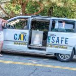 CAKE WALK: Juli Chapin, co-owner of CakeSafe, which produces a transportation system for safely moving cakes. Chapin is pictured on Torrey Road in South Kingstown, one of the town's steepest hills, using a CakeSafe to keep a cake in check on the steep incline. / PBN PHOTO/MICHAEL SALERNO