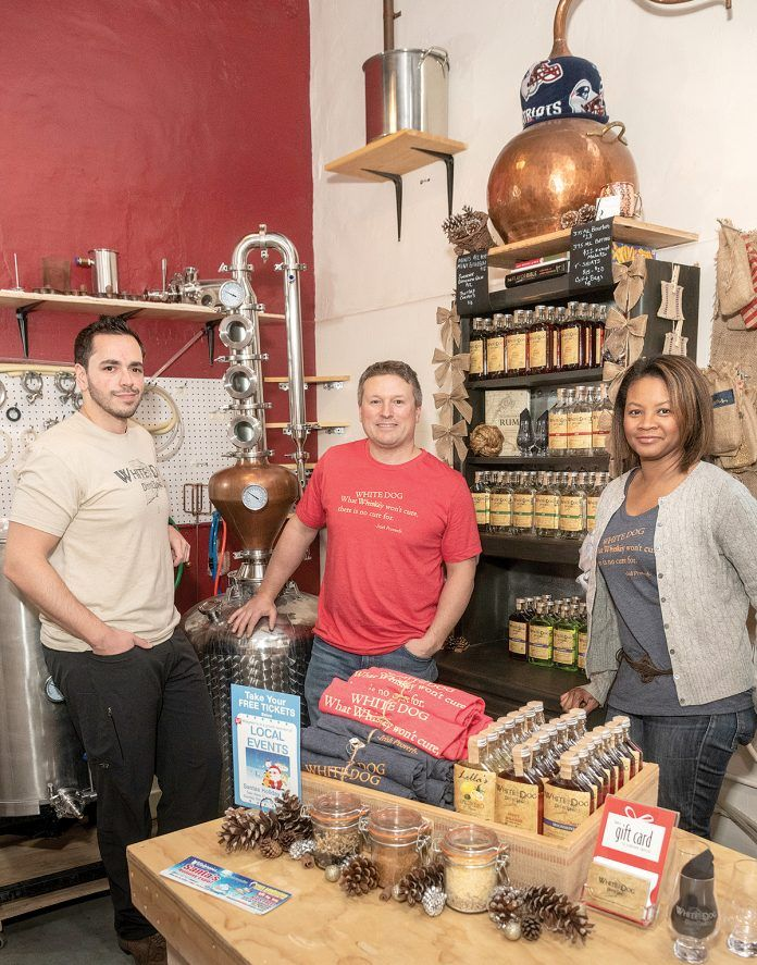 GROWING DISTILLERY: White Dog Distilling, incorporated as CAVE LLC, was founded in 2016 by Carlo Catucci, center, and his wife, Alecia, right, who partnered with longtime friends Eric Sylvestre, left, and Vin Greene, not pictured. Their micro-distillery and tasting room opened last April in a historic mill space in Pawtucket and will be moving to a larger retail location within the mill. / PBN PHOTO/MICHAEL SALERNO