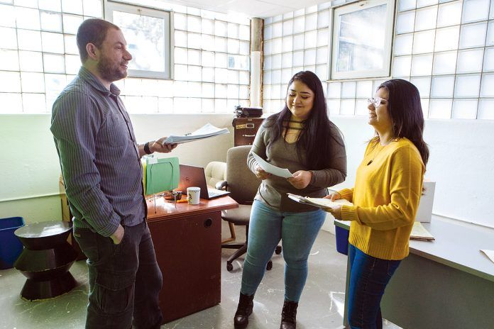MONEY MATTERS: From left, Andy Posner, founder and CEO of the Capital Good Fund, and loan officers Roxana Mercado and Ellie Parada discuss strategies for helping clients navigate debt and personal finance at the company's office in Providence.   / PBN FILE PHOTO/RUPERT WHITELEY