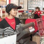 RAPID RESPONSE: Sejal Patel, foreground, co-owns the new Firehouse Subs franchise in Cranston. She's pictured with Alicia Martinelli, shift leader, and Sovannara Keo, crew member, in the background. The business collects donations for grants awarded to police and fire departments. / PBN PHOTO/MICHAEL SALERNO