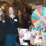AFTER HOURS: Dr. Day Care representatives Rebecca Compton, left, and Amy Vogel stand near their display, which includes a game wheel, during last year's Statewide Business After Hours networking event. This year's event will be held on March 26 at the Rhodes on the Pawtuxet in Cranston.   / COURTESY NORTHERN RHODE ISLAND CHAMBER OF COMMERCE