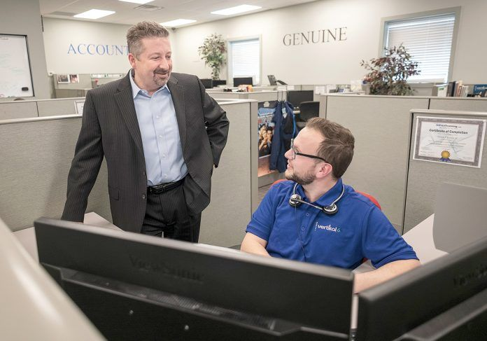 RECRUITING KEY: CEO Rick Norberg, left, speaks with Teddy Kennedy, service desk apprentice, at Vertikal 6 in Warwick. Norberg said the company's full-time apprenticeships have become the key to recruiting and developing employees. / PBN PHOTO/MICHAEL SALERNO