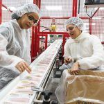 FOOD INSPECTORS: Employee Maria Velez, left, and CEO Navyn Salem check food packages as they move along the production line at the Edesia plant in North Kingstown. / PBN PHOTO/RUPERT WHITELEY