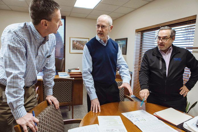 MEETING OF THE MINDS: Toray Plastics President and CEO Michael Brandmeier, center, discusses company business with Chris Nothnagle, left, corporate marketing senior director, and Chief Financial Officer David Jose. / PBN PHOTO/RUPERT WHITELEY