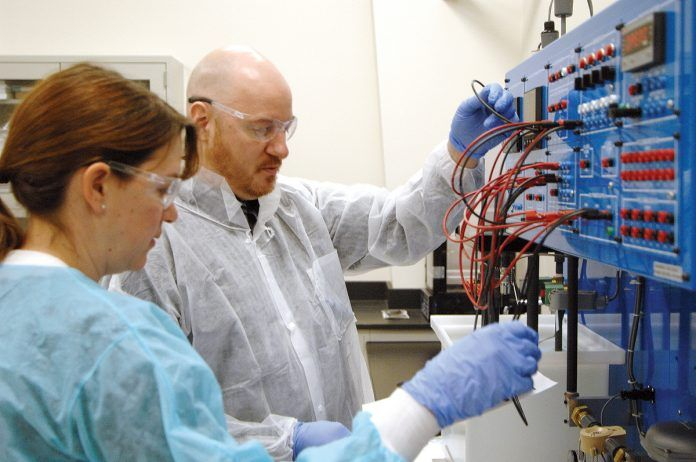 TEACHING TOOL: Megan Cortesi and Jeremy Demers, students in the process technician program at the Westerly Education Center, use a teaching tool that mimics industrial systems in the handling of liquids. / PBN PHOTO/BRIAN MCDONALD