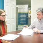 FINANCIAL PLANNING: Jeffrey Kreyssig, owner of Padgett Business Services, meets with client Abbey Dyer, office manager for Narragansett Property Management, in his Narragansett office. / PBN PHOTO/DAVE HANSEN