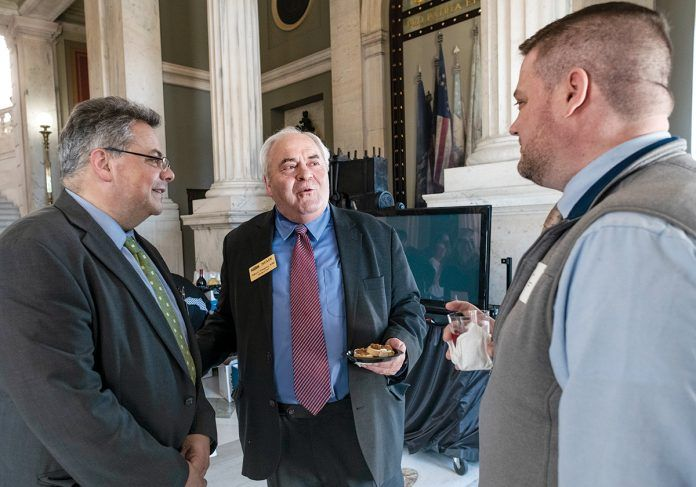 LEGISLATIVE RECEPTION: Lobbyist George Zainyeh, left, speaks with Northern Rhode Island Chamber of Commerce President and CEO John Gregory, center, and Robert Wheeler, owner of dog day care center Friends of Toto in Pawtucket, during the Rhode Island Chamber of Commerce Coalition's annual legislative reception at the Statehouse on March 26.   / PBN PHOTO/MICHAEL SALERNO