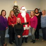 IN THE SPIRIT: Members of the Carey, Richmond & Viking staff mark the holidays with a visit from Santa. / COURTESY CAREY, RICHMOND & VIKING INSURANCE