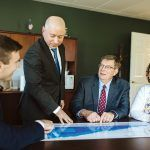 HUDDLE UP: Edward Jones financial adviser Eric Milhoua, standing, talks numbers with, from left, advisers Tom Gardiner and Frank Wallington, and office administrator Ashley Bickford, in Westerly. / PBN PHOTO/RUPERT WHITELEY