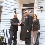 RENOVATED HOME: Homeowner Carlos Reyes, left, is pictured with Providence Mayor Jorge O. Elorza and Smith Hill Community Development Corp. Executive Director Jean Lamb in front of his home at 120 Camden Ave. during ceremonies to celebrate homeowners moving into houses renovated under the city's EveryHome program. / COURTESY CITY OF PROVIDENCE