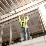 CONSTRUCTION EMPLOYMENT in the Providence metro area increased 1% year over year to 25,800 jobs in June. Above, Journeyman glazer Michael Bennacchia of Chandler Architects works on the interior window frame during renovation of the Empire Street wing of the Providence Public Library. / PBN FILE PHOTO/MICHAEL SALERNO