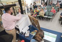 ONLINE PRESENCE: Auctioneer Travis Landry takes bids from the crowd, as well as online, during an auction at the Bruneau & Co. Auctioneers gallery in Cranston. Gallery owner and President Kevin Bruneau said most of their auctions feature online bidders from around the world competing with live audiences, pulling in up to 10,000 additional bidders who check in on auctions periodically. / PBN PHOTO/MICHAEL SALERNO