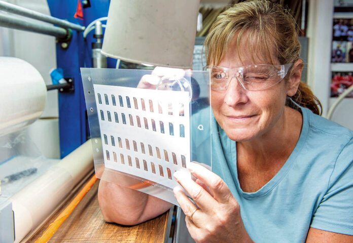 A CLOSE LOOK: NFI Corp. employee Kim Brittain inspects a laminate at the New Bedford company.PBN PHOTO/DAVE HANSEN