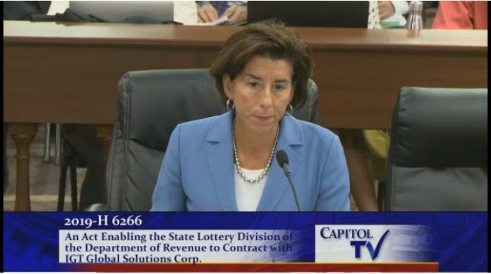 GOV. GINA M. RAIMONDO testified Tuesday in favor of a negotiated 20-year contract with IGT to continue to manage the state lottery.