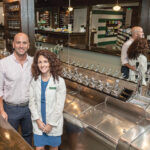 READY TO SERVE: Christina and Ken Procaccianti stand at the soda counter inside Green Line Apothecary in Providence, a throwback to independent pharmacies of an earlier era.  / PBN PHOTO/MICHAEL SALERNO