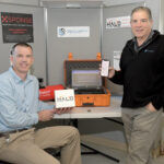 UNCOMMON SENSOR: Tom Reilly, left, general manager at Security Supply Inc. in Cranston, and Rick Gentile, a sales representative, display equipment that can detect the vapors created by e-cigarettes. The detectors send email and phone alerts when an alarm goes off. / PBN PHOTO/MIKE SKORSKI