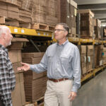 PAPER PUSHERS: David Spencer, right, CEO of Atlantic Paper & Supply, talks with sales representative Sean Borek. Spencer runs the company with his wife, Lisa, whose grandfather started the business in the 1940s. / PBN PHOTO/MICHAEL SALERNO