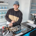 UP IN SMOKE: White Horse Vapor employee Joey Chen shows some of the products the vape shop carries. Owner Dino Baccari said a recent statewide ban on flavored e-cigarettes forced him to close his White Horse Vapor location in Warwick. / PBN PHOTO/MICHAEL SALERNO