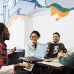 HIGHER LEARNING: From left, College Crusade of Rhode Island high school adviser Agi Kah and middle school advisers Manuela Garcia, Victor Martinez and Eric Rossi have a conversation at the organization's Providence headquarters. / PBN PHOTO/RUPERT WHITELEY