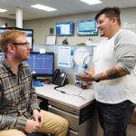 SHOP TALK: Vertikal6 service desk apprentices Steven Walsh, left, and Dylan Herrera share a conversation in the company's office. / PBN PHOTO/RUPERT WHITELEY