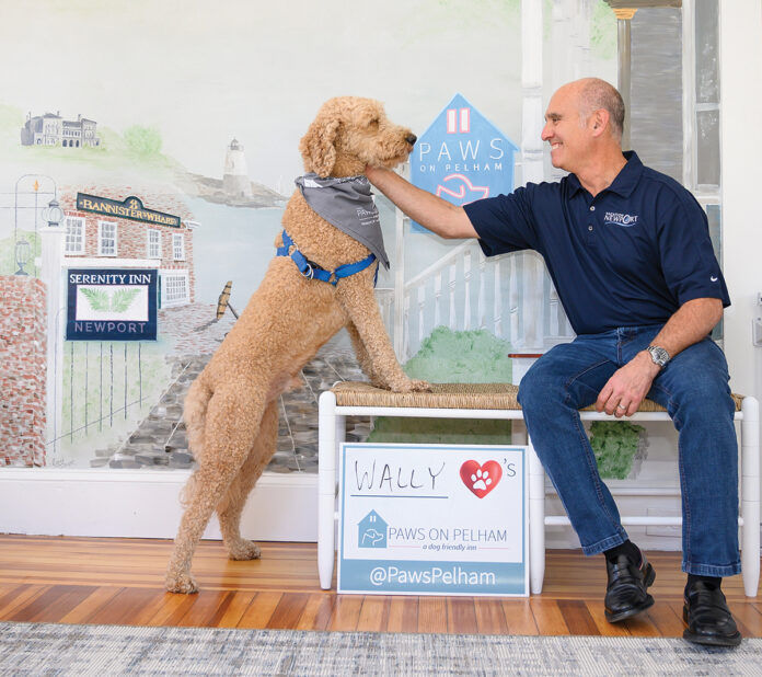 HOUND HOSPITALITY: Chris Bicho, president of Landings Real Estate Group, which owns the Newport inn Paws on Pelham, greets Wally, a goldendoodle, in the lobby. / PBN PHOTO/DAVE HANSEN