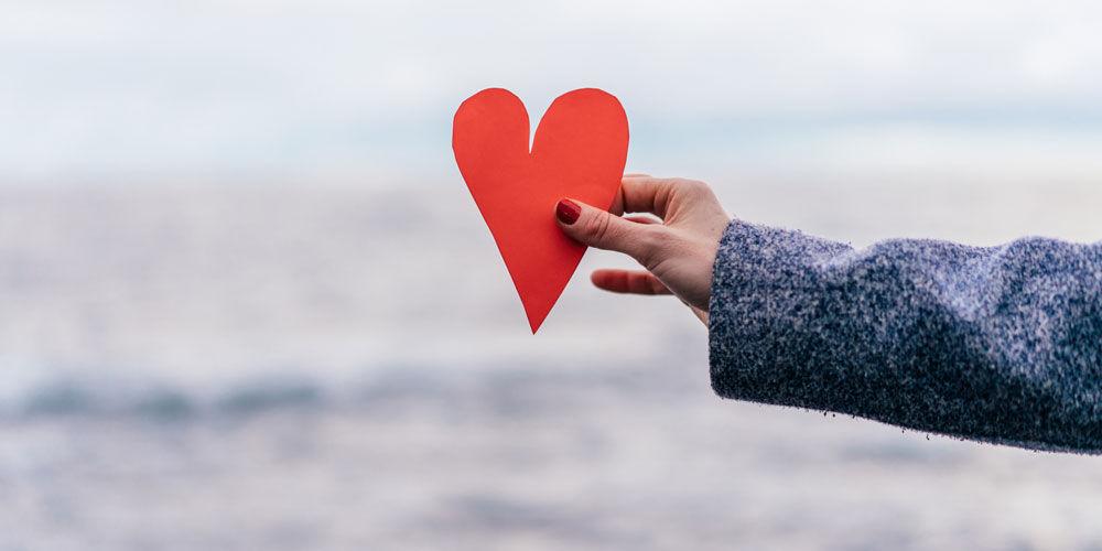 Hånd holder et hjerte med havet i bakgrunnen
