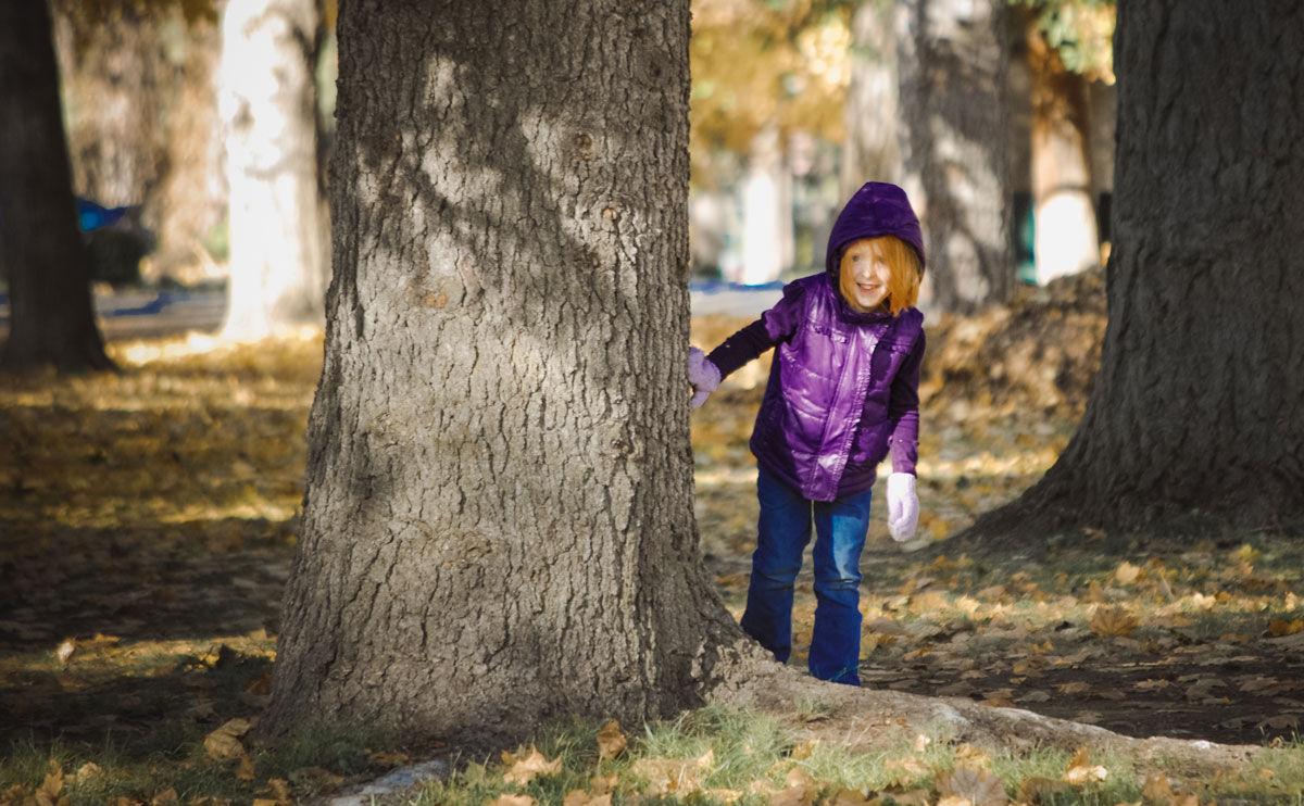 Jente titter frem fra et tre