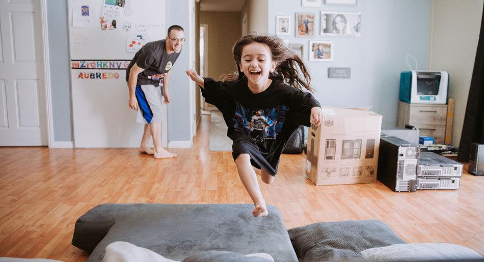 Glad jente løper og hopper opp i sofa