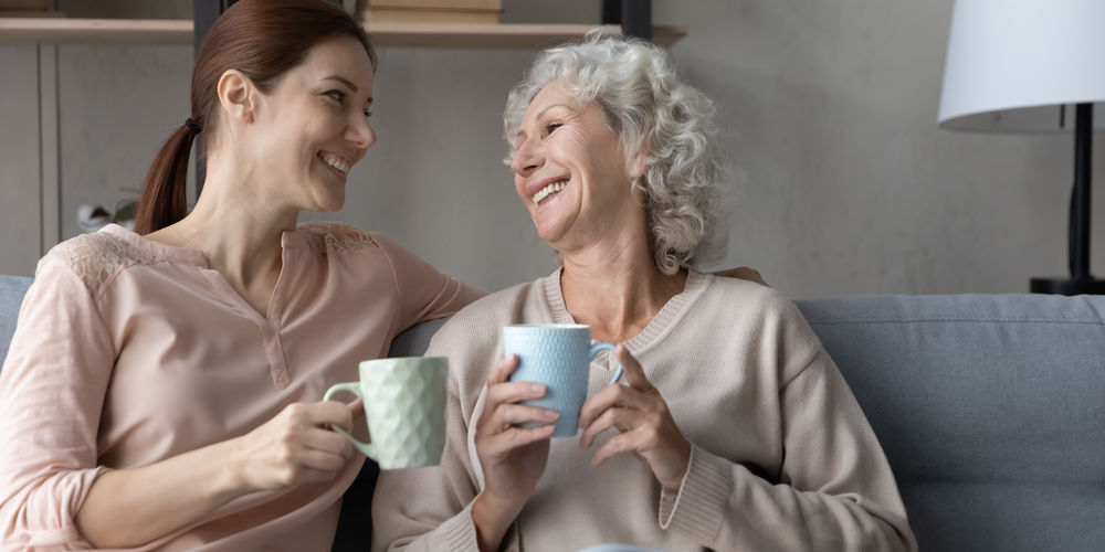 Image of a woman having a cup of coffee with her older mother