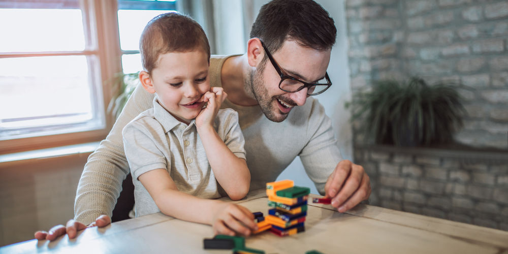 Image of a boy playing with blocks with his father